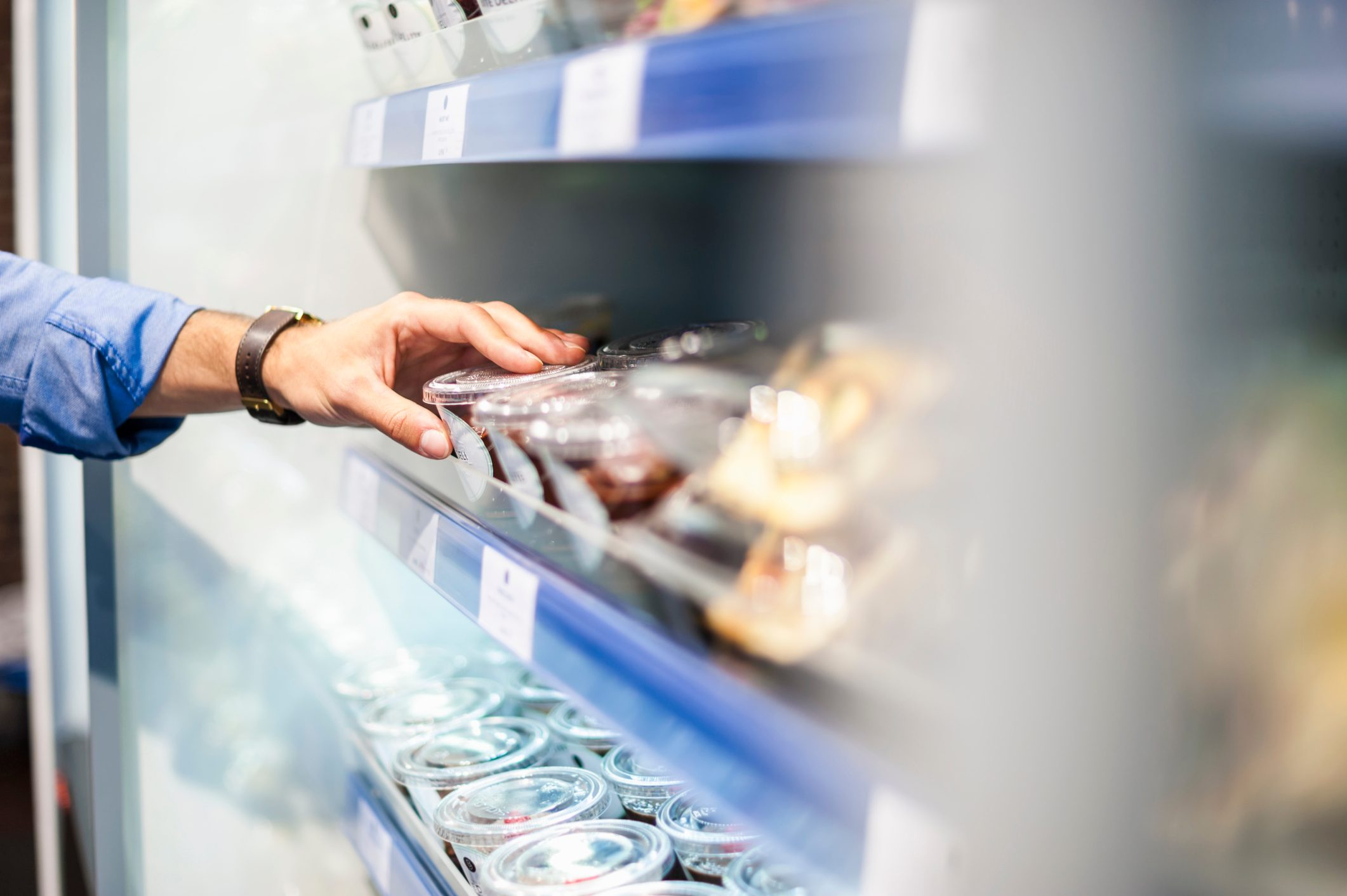 close up of man's hand taking food from shelf at the store