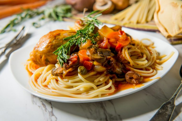 Italian chicken Cacciatore hunter's stew with spaghetti noodles and crusty bread