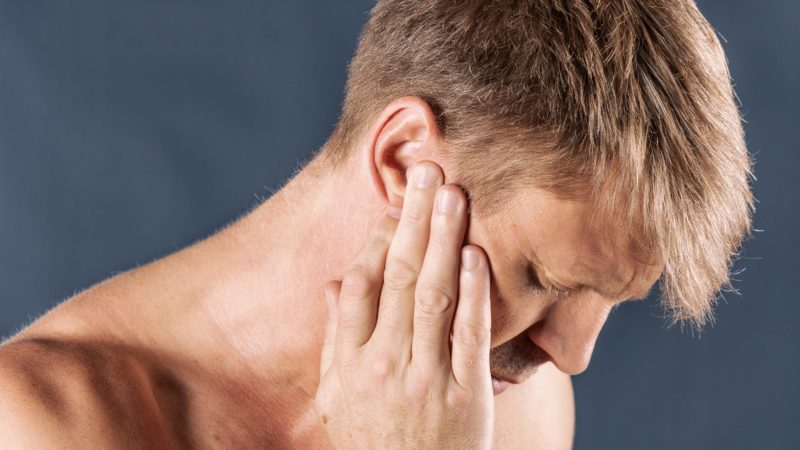 Man has a sore ear. Man suffering from headache on blue background