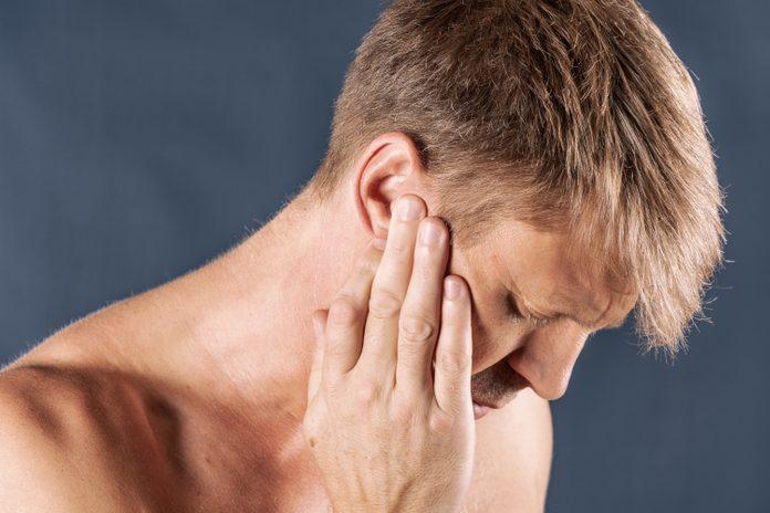 Man has a sore ear. Man suffering from headache on blue background