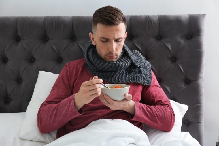 Sick young man eating broth to cure cold in bed at home