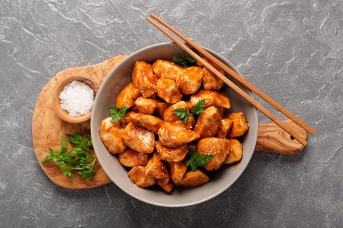 bowl of orange chicken with chopsticks