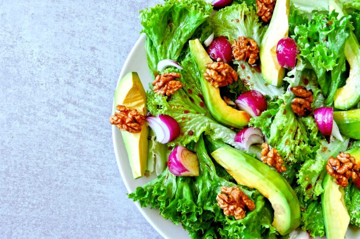 Useful salad on a plate. Salad with avocado and greens. Vegan salad with walnuts.