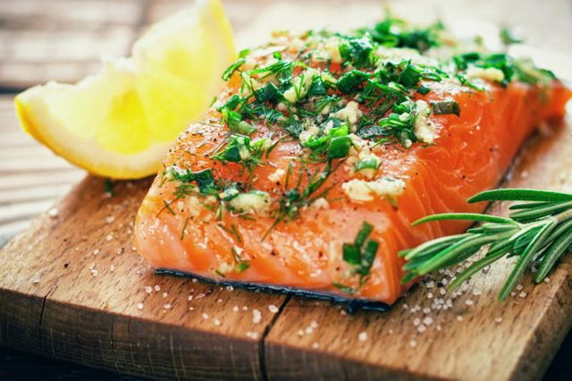 Delicious salmon on cutting board with lemon