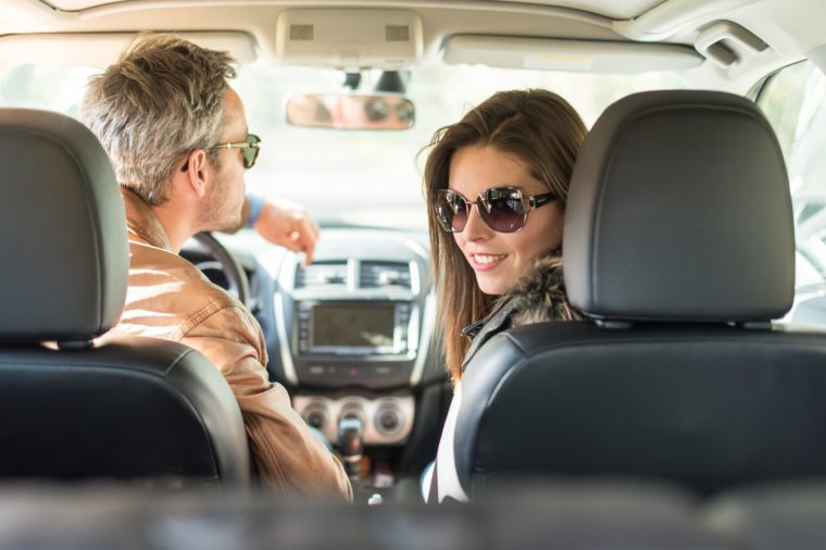 Rear view of a middle aged couple in a black seats car. They are about to leave for the weekend, wearing their leather coats and sunglasses. The smiling woman is looking at camera