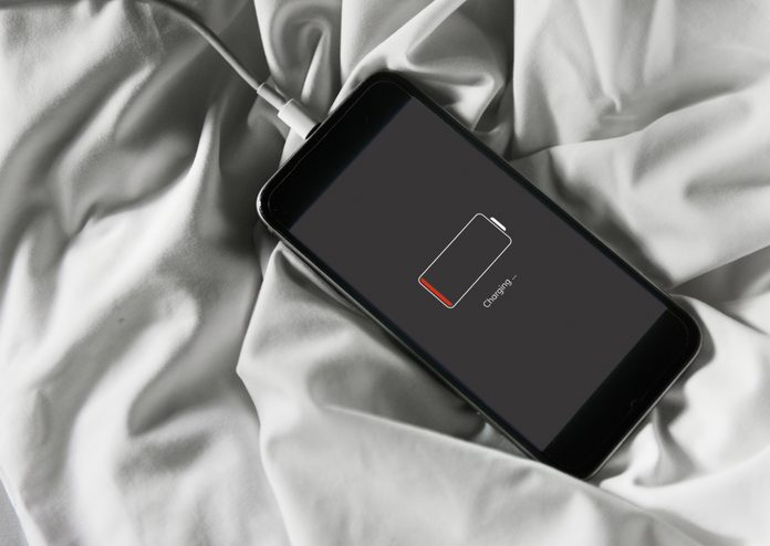 Closeup of out of battery mobile phone charging and lying on white fabric background