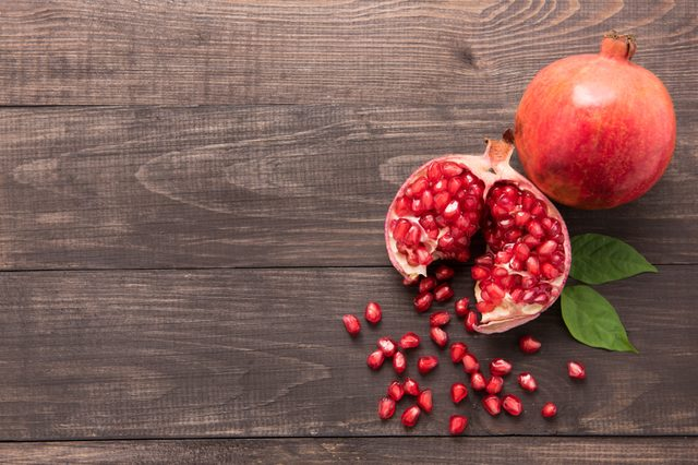 Ripe pomegranate fruit on wooden vintage background.