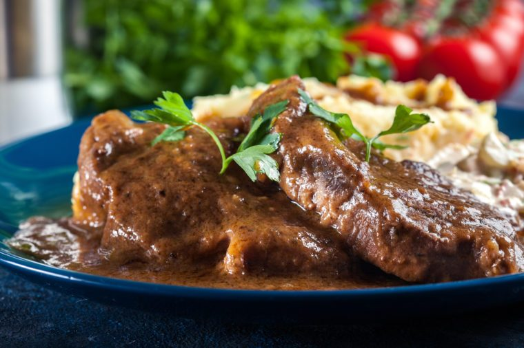 Stewed pork neck in sauce. Served with mashed potatoes and salad
