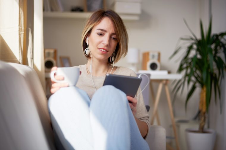 Woman sitting on sofa and using tablet.