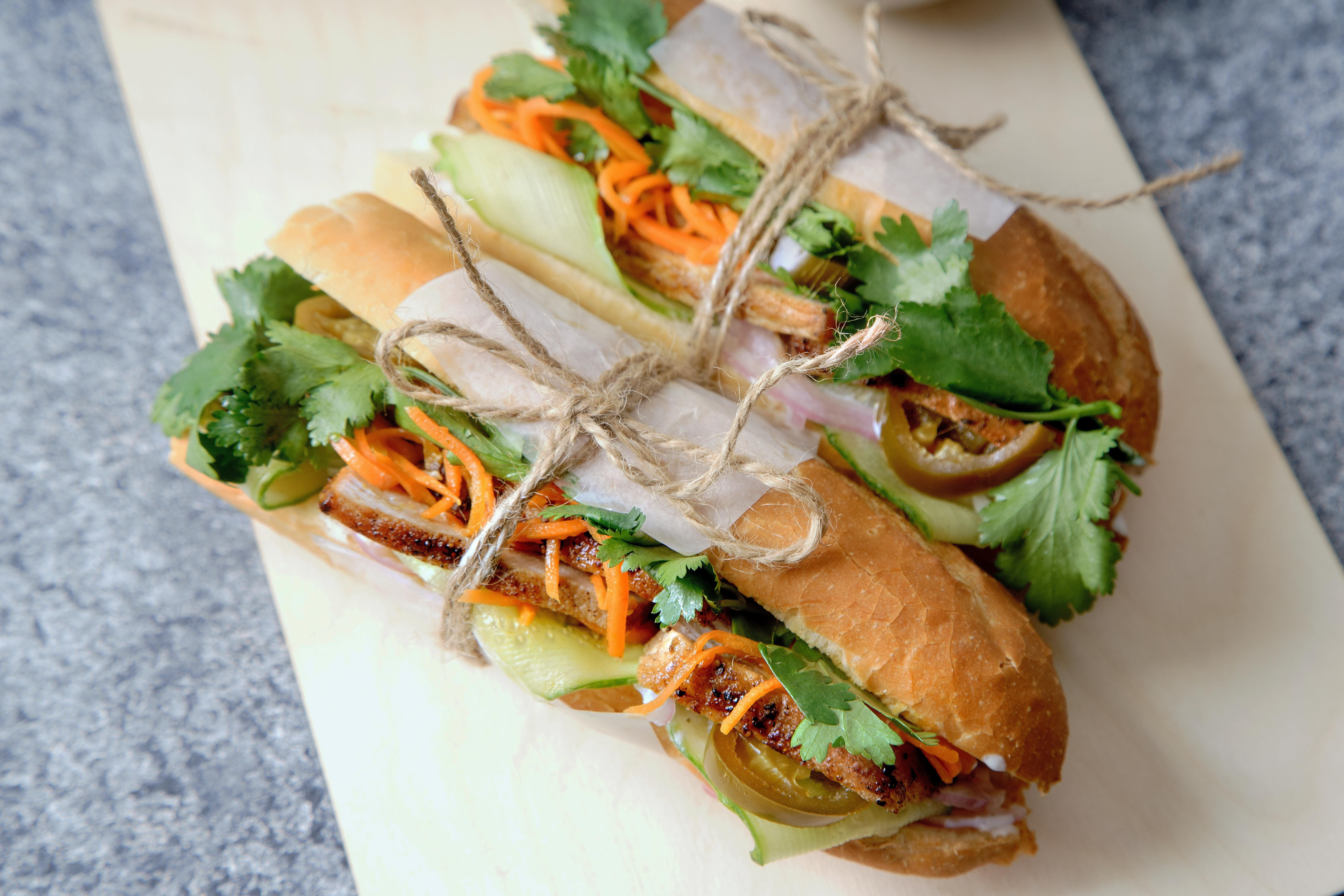 sub sandwich with sliced grilled pork tenderloin, tied with twine