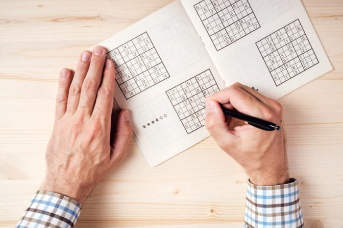 Top view of male hands solving sudoku puzzle on wooden office desk