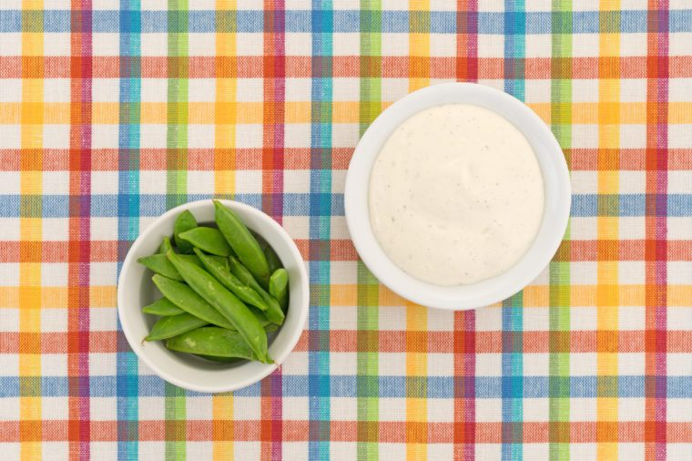 Top view of a small bowl filled with sugar snap peas and creamy ranch dressing to the side atop a colorful cloth patterned place mat.
