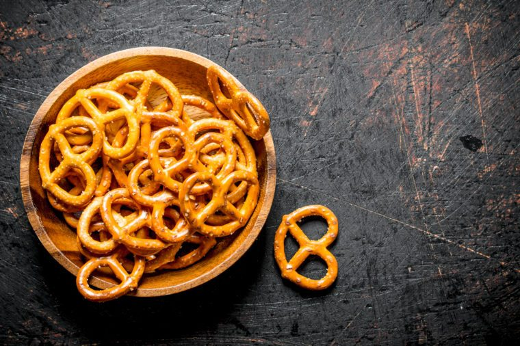 Snacks pretzels in a bowl. On dark rustic background