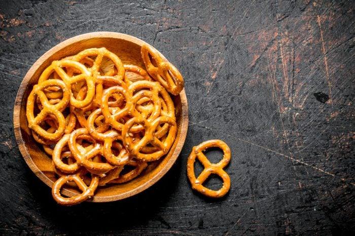 Snacks pretzels in a bowl. On dark rustic background