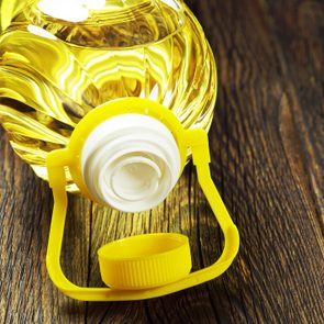 Vegetable oil in plastic bottle on old wooden table closeup