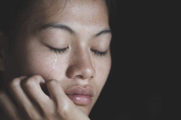 woman crying tears eyes closed dark