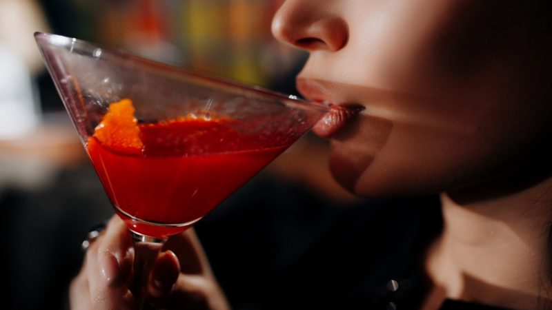 young girl drinking red lip cocktail close up.