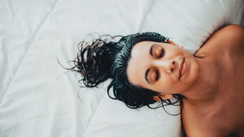 Portrait of young brunette woman just getting out of the shower with wet hair on the bed