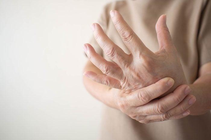 woman rubbing her hand pain
