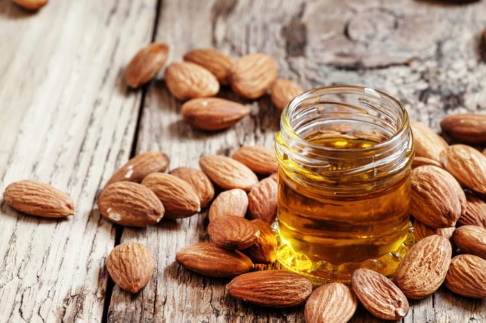 Sweet Almond Oil, first extraction, in a small glass jar, dry almond nuts on an old wooden background, selective focus