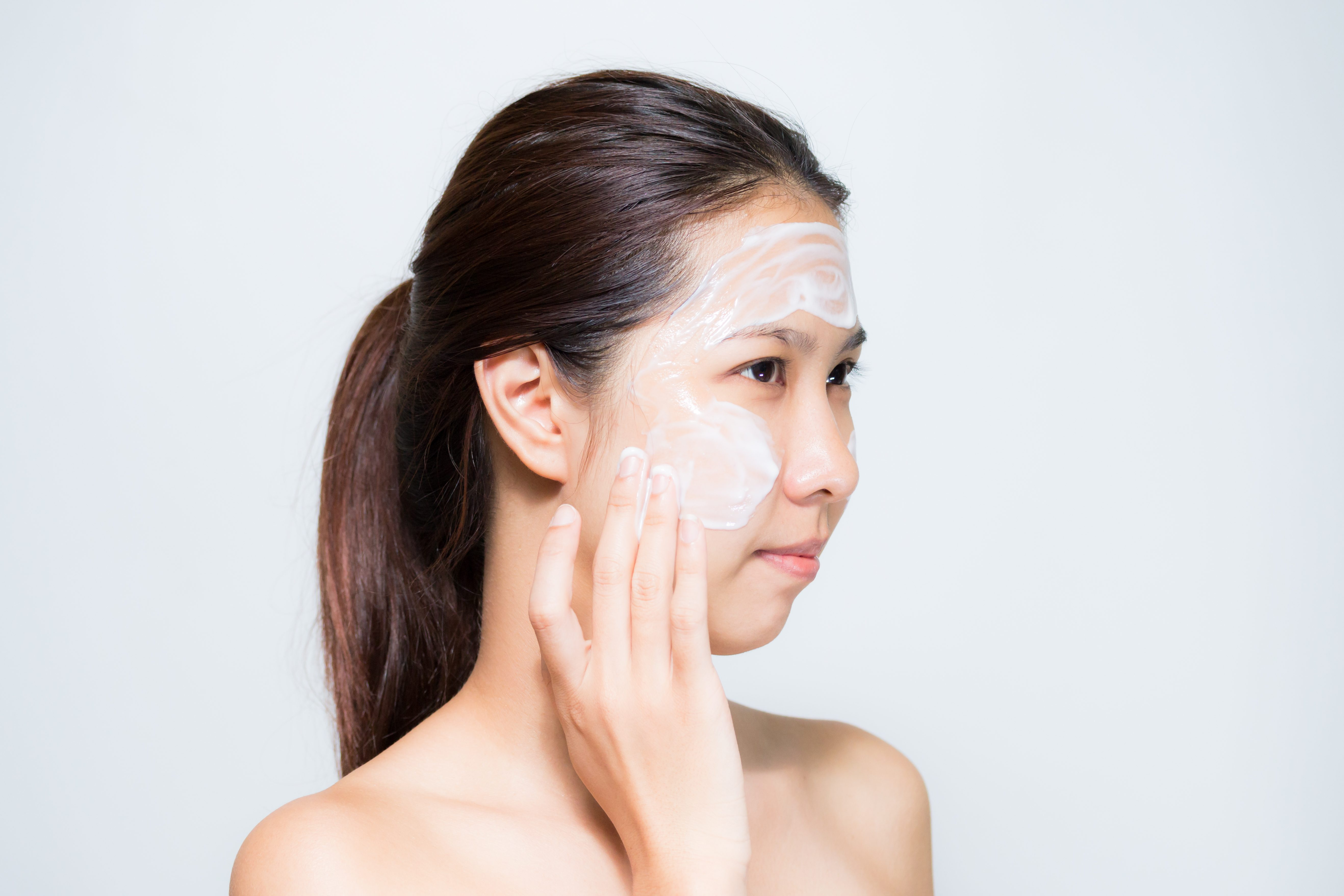Beautiful Young Woman applying facial Mask yogurt . Spa and skin care concept