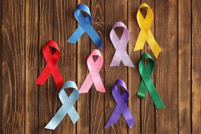 Different ribbons on wooden background. Cancer awareness concept