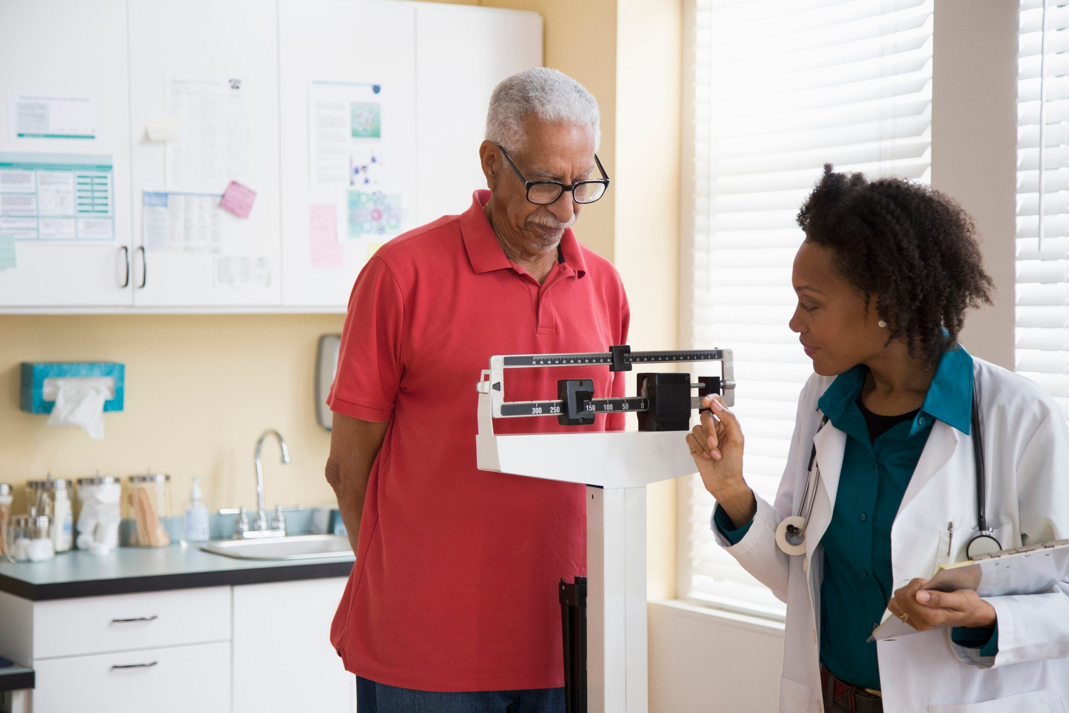 senior man standing on weight scale at the doctor