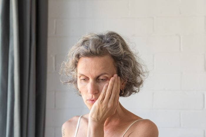 woman with hand on face