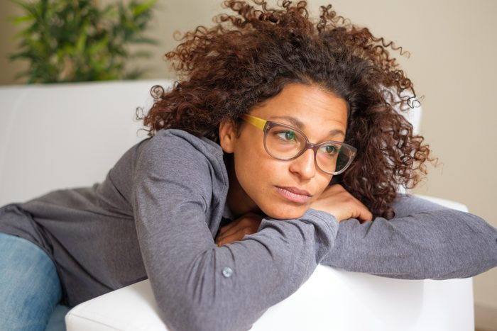 woman laying on couch at home exhausted and worried