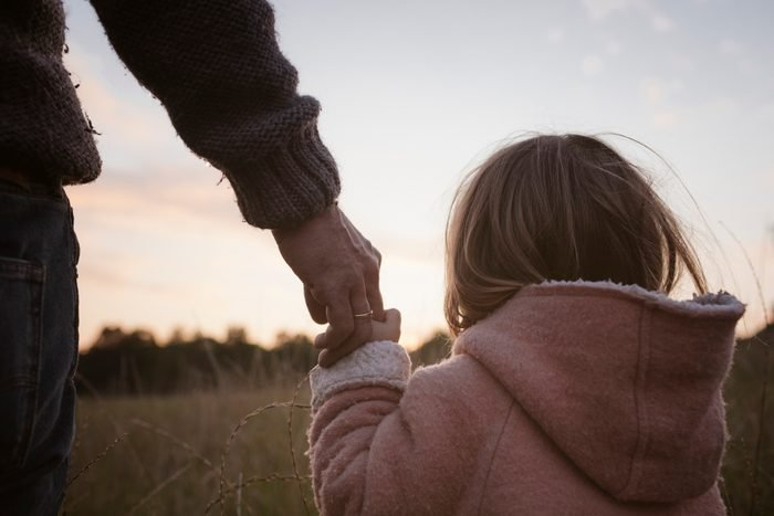 Father and daughter holding hands in field