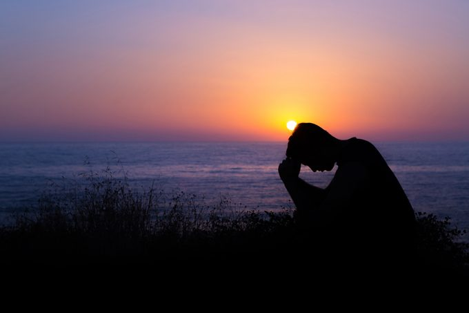 silhouette of sad man sitting on the beach during sunset