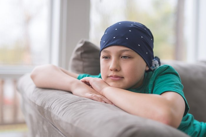 child with cancer sitting on couch