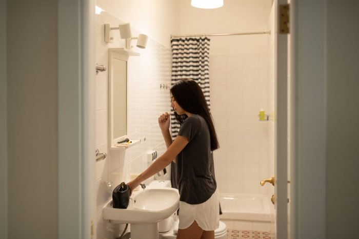 young woman brushing teeth in bathroom before bed