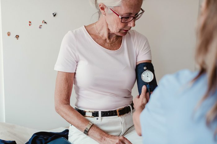 woman having blood pressure checked in doctor's office