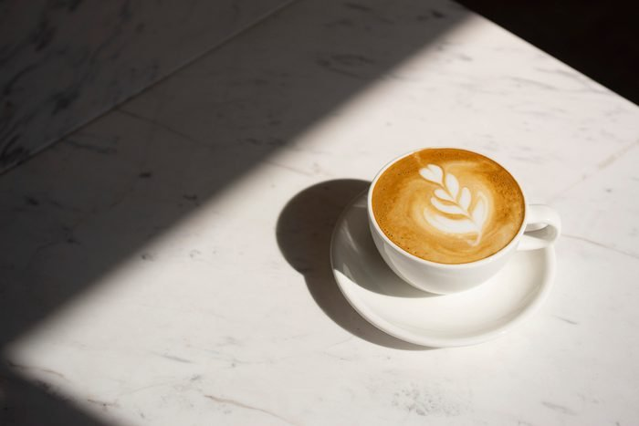 cappuccino coffee on table with sun shining
