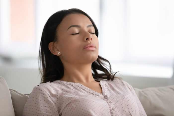 woman taking a deep breath while sitting on couch at home