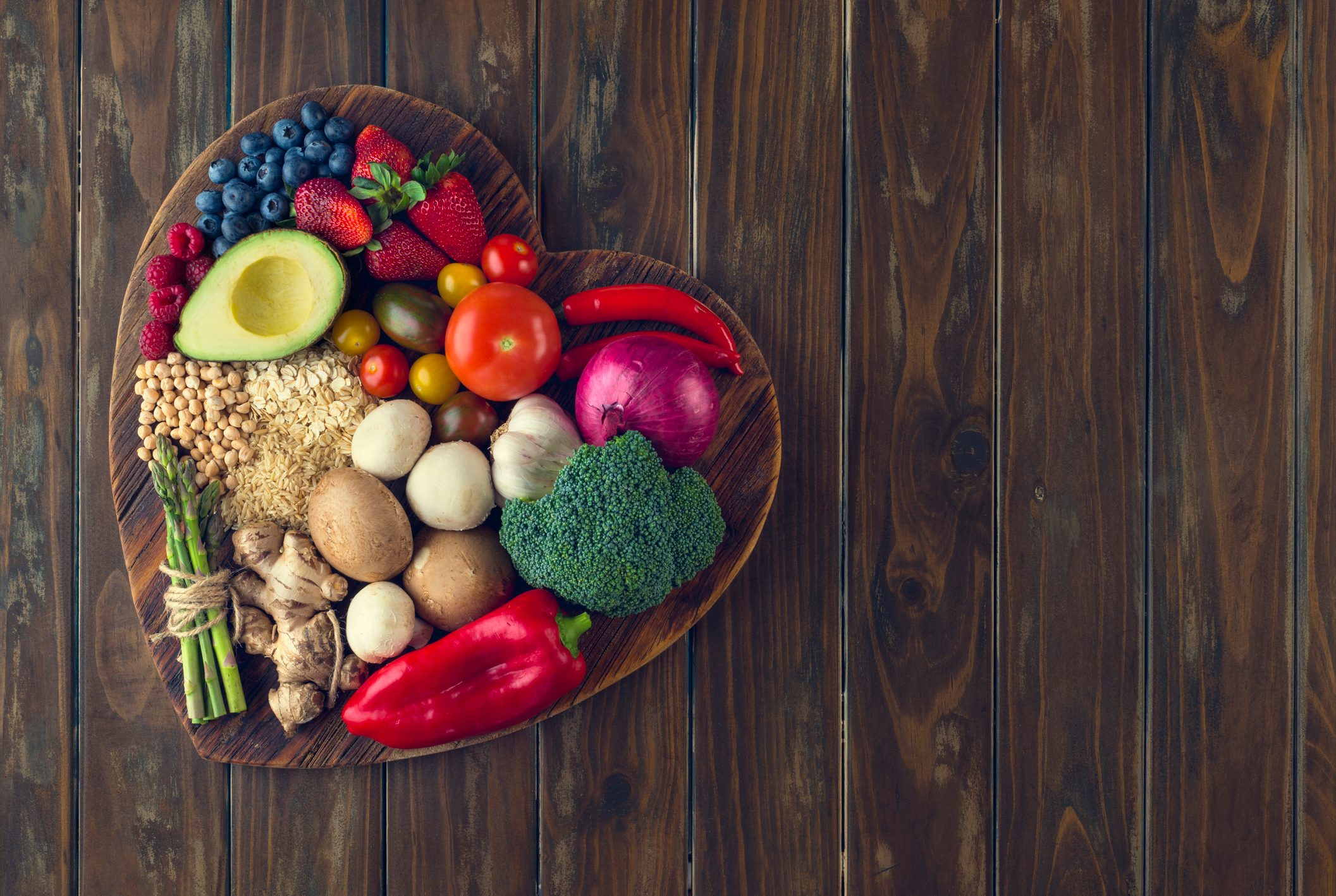 healthy foods in the shape of a heart on wood background
