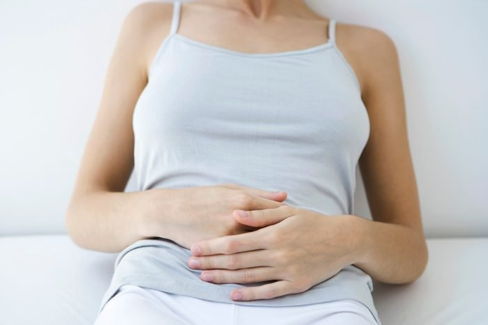 close up of woman holding her stomach