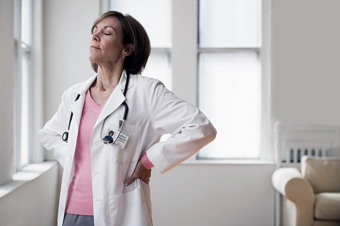 female doctor taking a deep breath in office