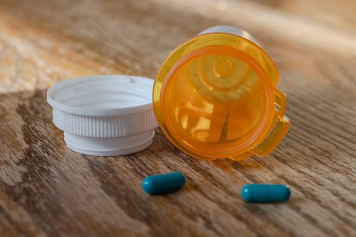 Prescription pill bottle with last two blue pills spilling onto wooden kitchen table. Close up view.