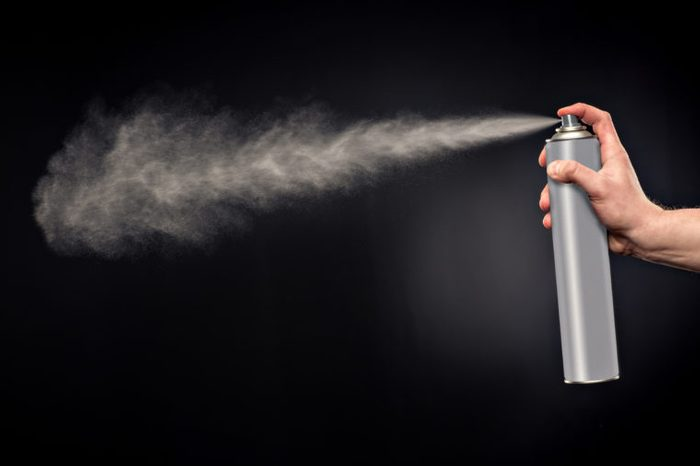 Close-up view of human hand and spray bottle isolated on black