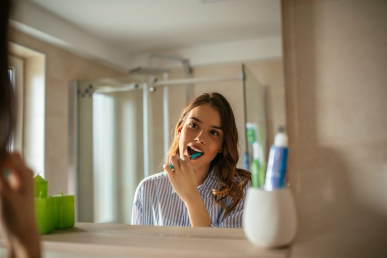 young woman brushing her teeth