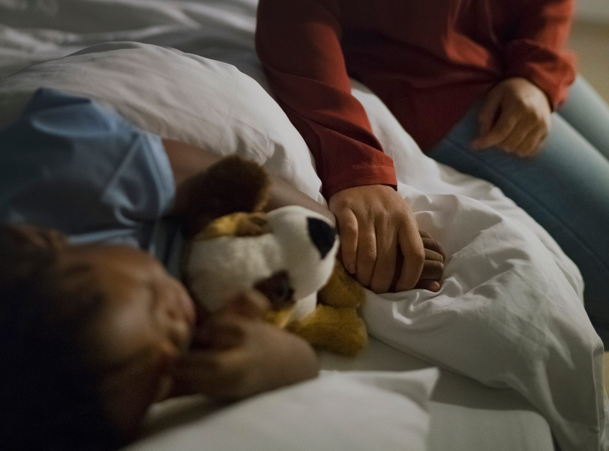 mother holding son's hand in hospital bed