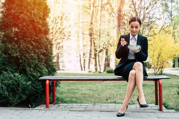 Modern beautiful business woman in a black business suit sits on a bench outside and eats a salad with fresh vegetables