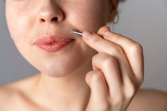 A young woman plucks her hair over her upper lip with tweezers. The concept of getting rid of unwanted facial hair. Close up