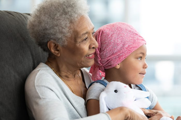 young girl with cancer sitting on her grandma's lap