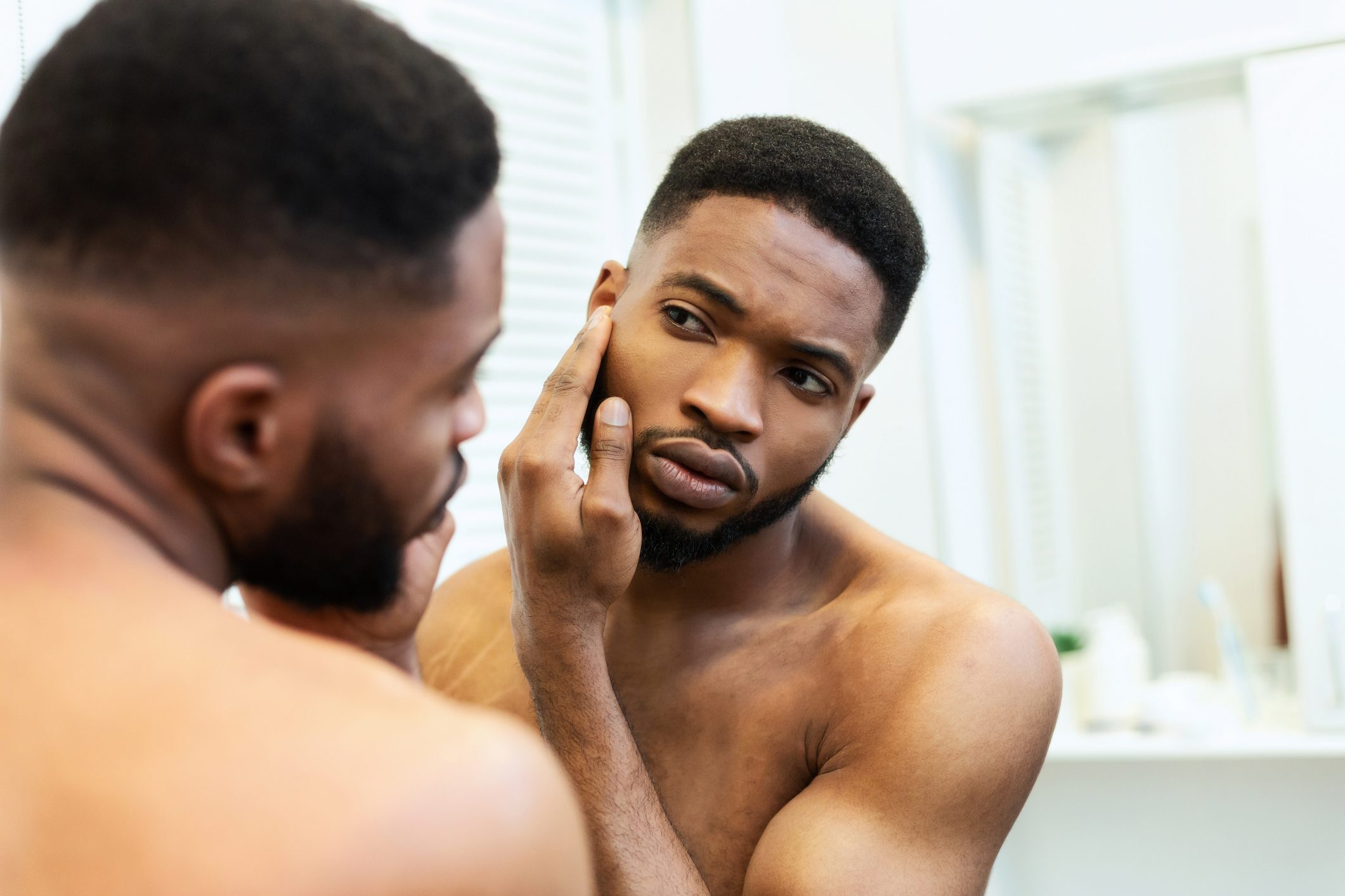 man looking at face in mirror