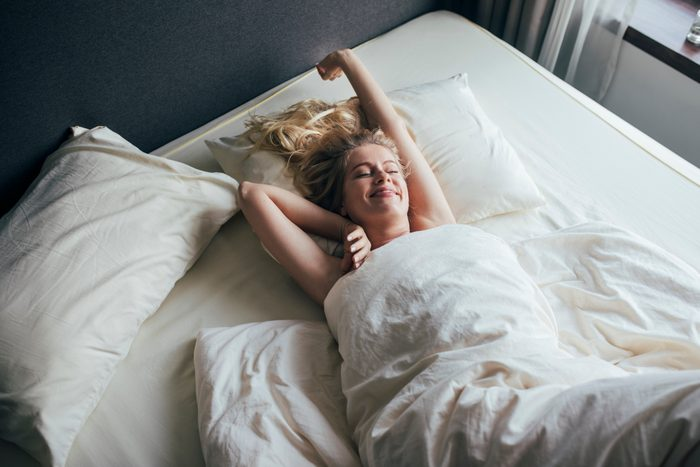 young woman waking up in the morning smiling