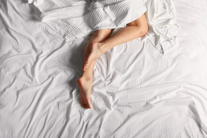 overhead shot of woman's legs on bed