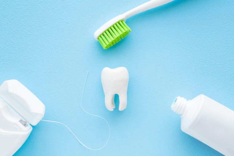 Tube of toothpaste, toothbrush with green bristle and container of dental floss around white tooth on pastel blue background. People teeth hygiene. Closeup.